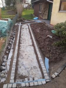 Bau der Randeinfassung aus Basaltkleinpflaster aug Drainagematte
